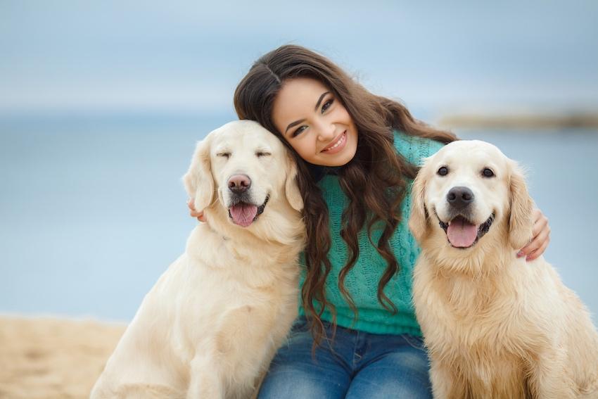 Junge Frau lächelt mit zwei grinsenden Labrador Hunden am Strand